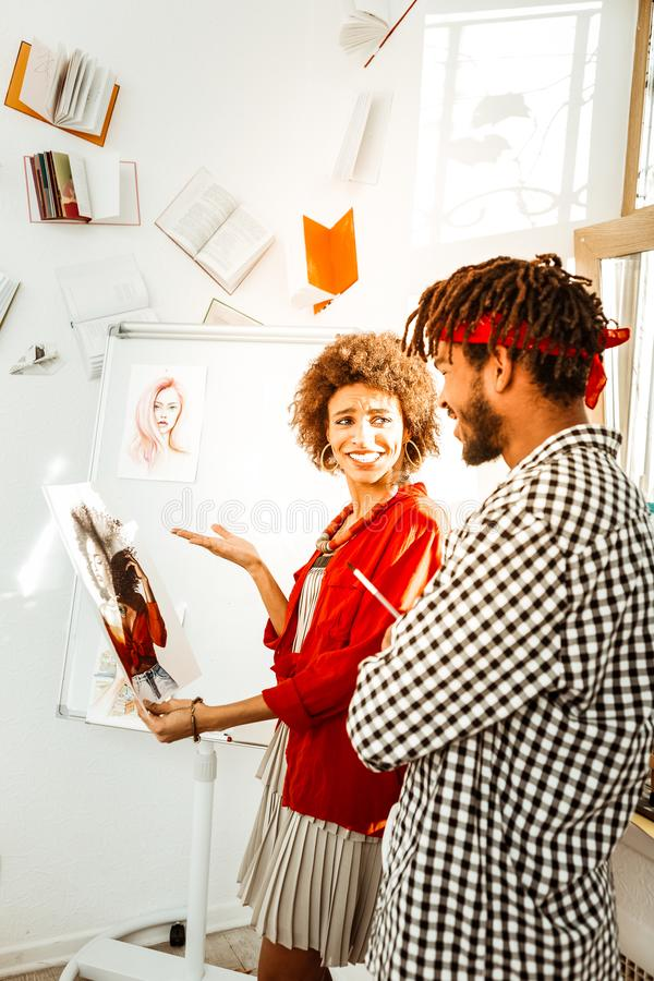 Handsome loving bearded man giving portrait of his girlfriend to her. Giving portrait. Handsome loving bearded men with dreadlocks giving portrait of his royalty free stock photo