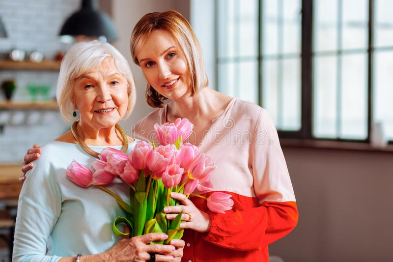 Beautiful mature daughter giving tulips to wrinkled grey-haired mother royalty free stock image