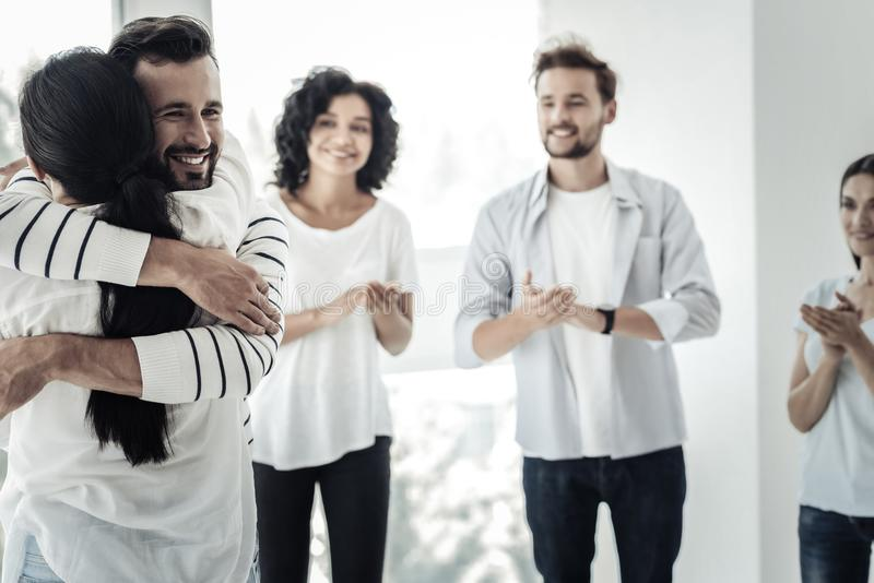 Nice delighted man hugging his friend stock image