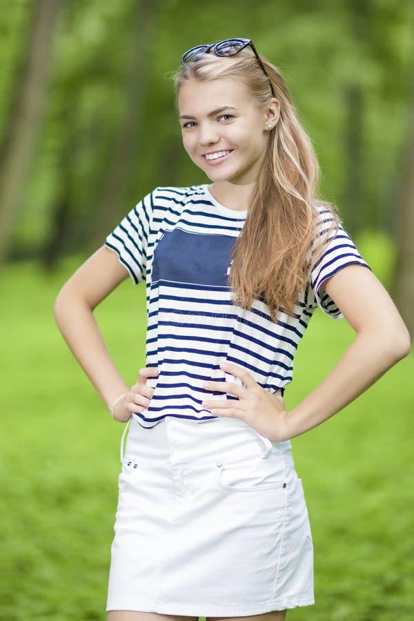 Giwl adolescent de sourire heureux dans le T-shirt rayé posant dehors images stock