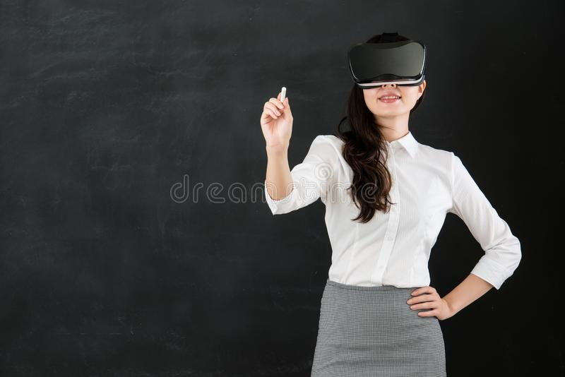Giz asiático da escrita do professor da mulher com auriculares de VR imagem de stock