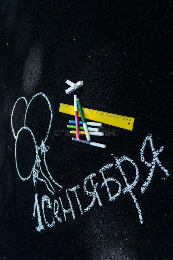 Giz branco na inscrição preta do asfalto russo o 1º de setembro linha amarela, marcadores coloridos, bolas pintadas fotografia de stock royalty free