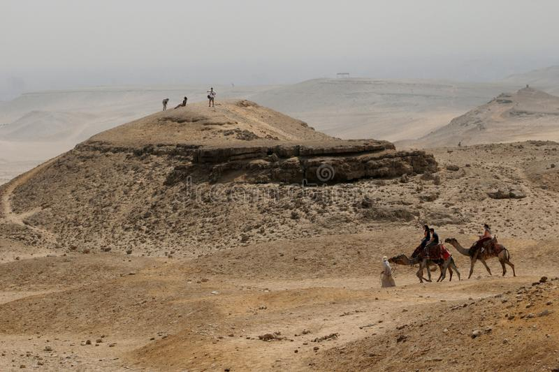 An Arab man leads camels through the desert. The Giza Plateau. T stock photography