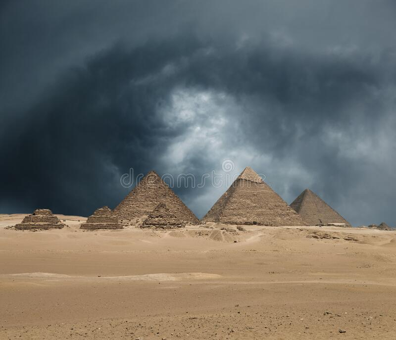 The Giza pyramid complex under dramatic grey stormy sky stock photos