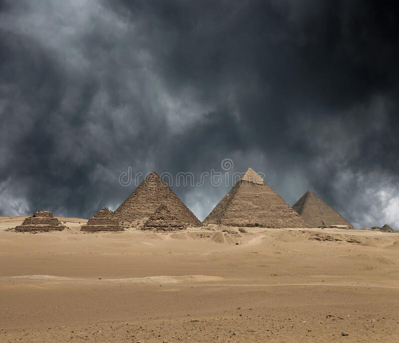 The Giza pyramid complex under dramatic grey stormy sky royalty free stock photography