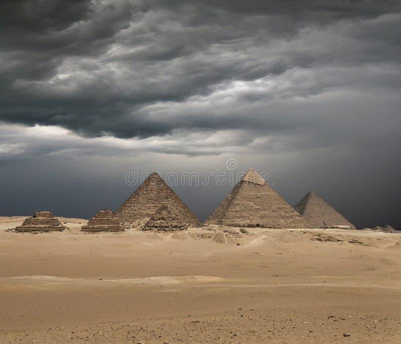 The Giza pyramid complex under dramatic grey stormy sky royalty free stock photos