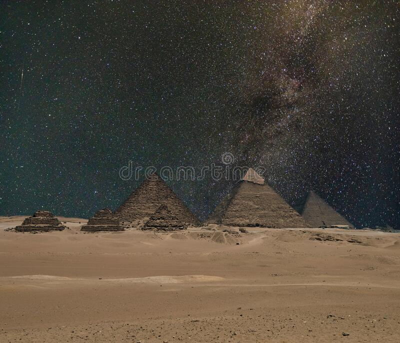 The Giza pyramid complex under night starry sky stock image