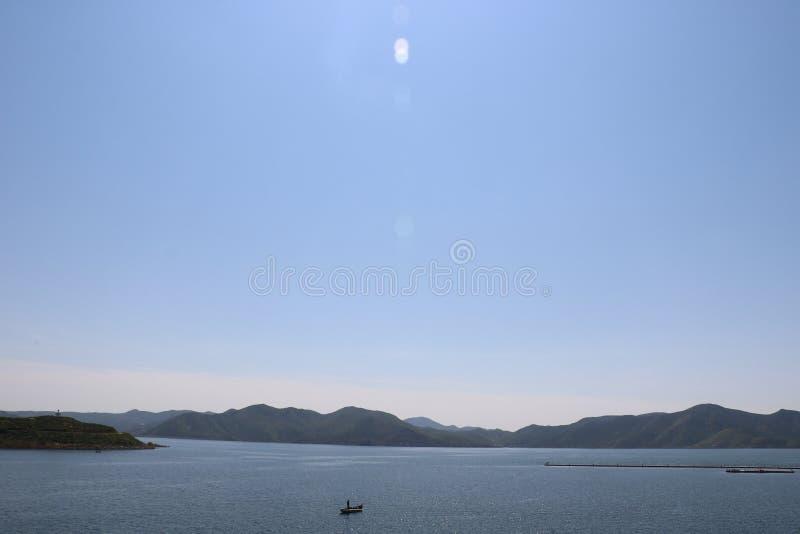 Gjord ensam roddbåt på en stillhet, blå sjö som omges av kullar arkivfoto