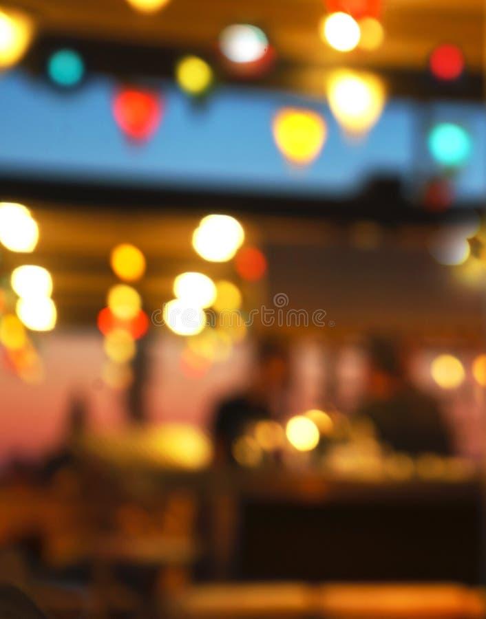 Gjord suddig bakgrund av folk som sitter på restaurangen, stången eller nattklubben med färgrik ljusbokeh royaltyfri fotografi