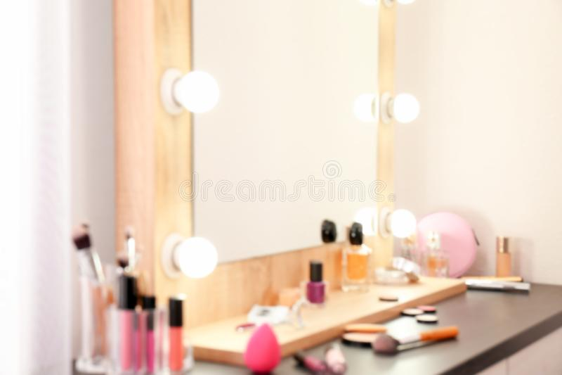 Gjord suddig sikt av tabellen med makeupprodukter och spegeln nära den vita väggen, closeup royaltyfri fotografi