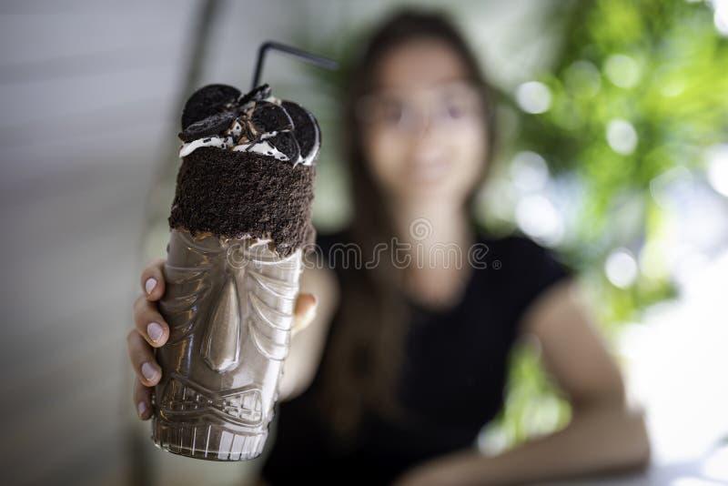 Gjorda suddig härliga kvinnor rymma en chokladskaka och kakor på ett genomskinligt exponeringsglas med infödd design royaltyfria bilder