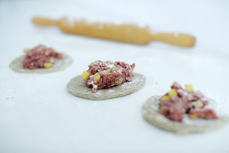 Gjorde Artfully hemlagade köttsmå pastejer på etttäckt köksbord arkivbilder