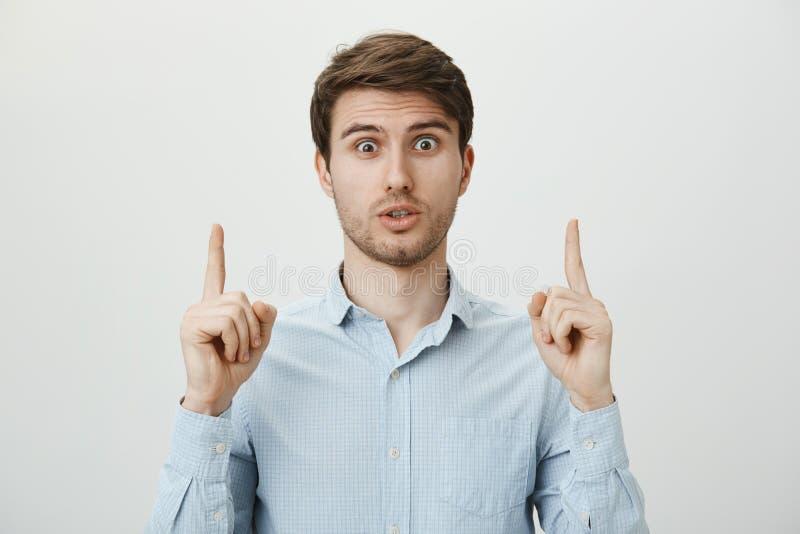 Gjorde dig såg också det Stående av den bedövade chockade stiliga mannen med borstet som pekar upp och ser med misstro och arkivfoto