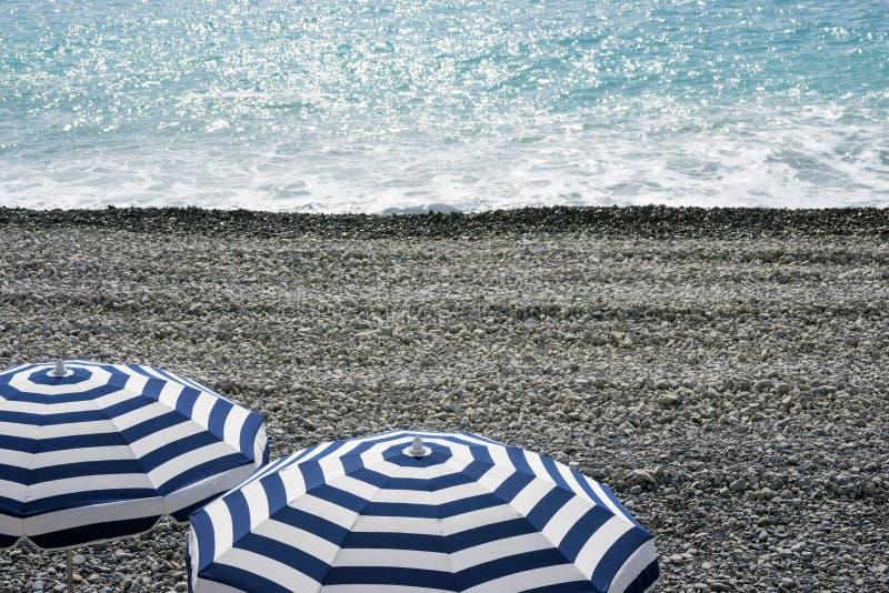 Gjorde randig blåa och vita paraplyer på ett Pebble Beach på Promenade des Anglais i Nice, Frankrike, väntar på gäster Blå arkivfoto