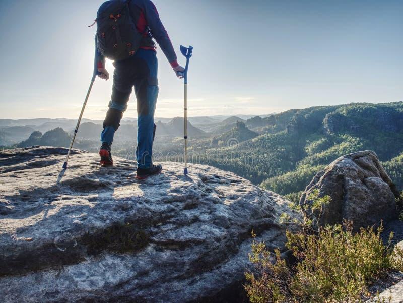 Gjort ont anseende för stark man med kryckor på bergtoppmöte royaltyfria bilder