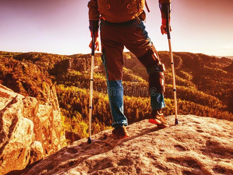 Gjort ont anseende för stark man med kryckor på bergtoppmöte royaltyfri bild