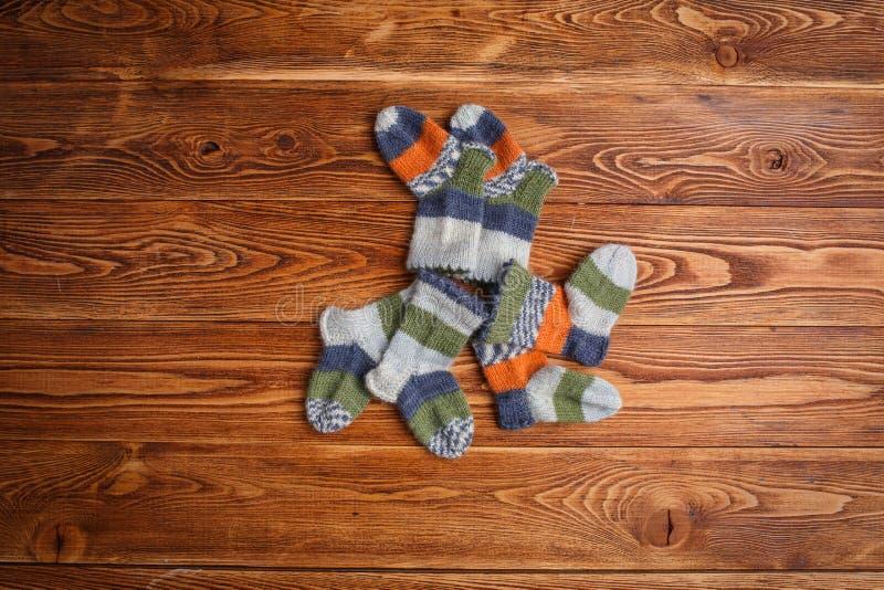 Gjort randig stuckit mångfärgat behandla som ett barn sockor på en träbakgrund arkivfoton