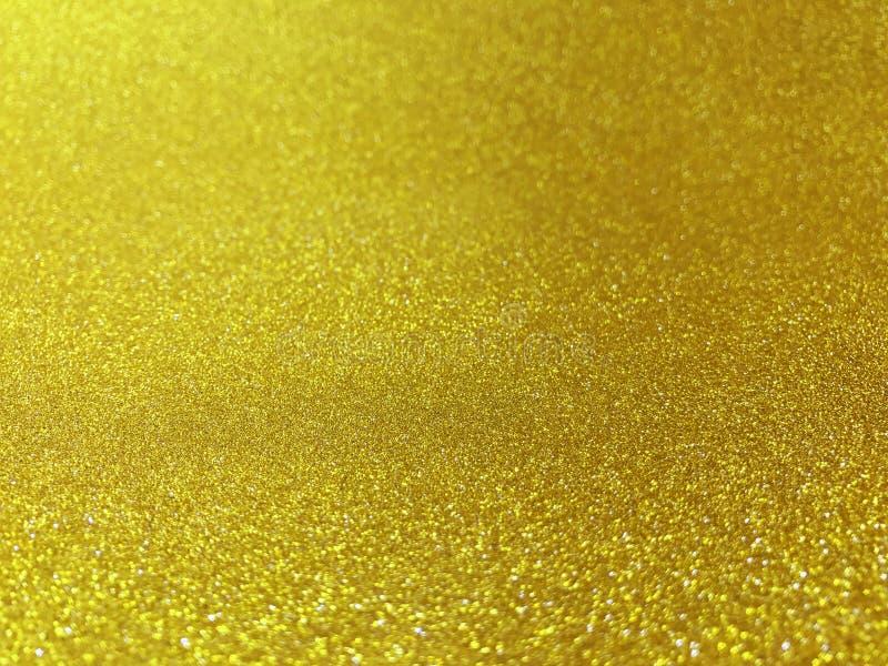 Gjort suddig ljust sken för guld- bildbokeh för glad jul firar blänker bakgrund som är härlig blänker bokehgnistrandet för guld-  arkivfoto
