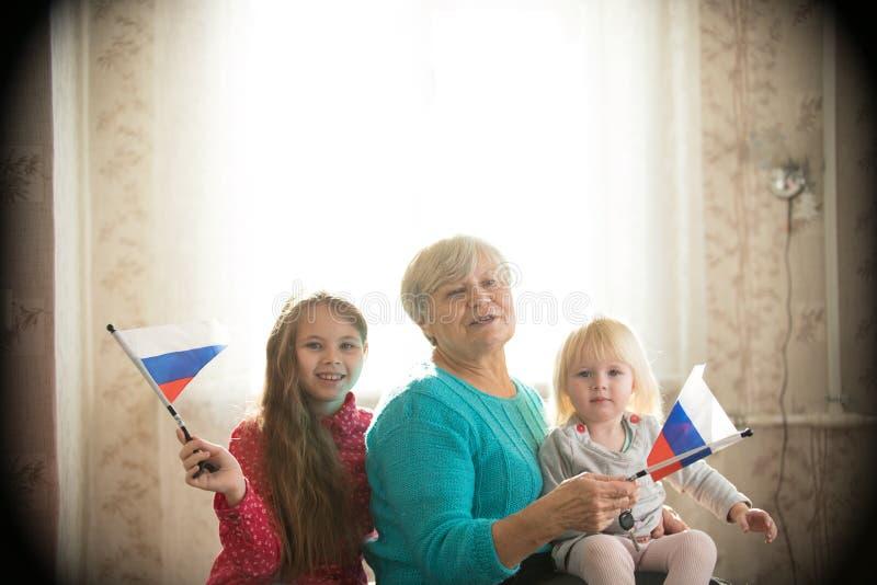 Glückliche Familie, die auf dem Bett sitzt Zwei Mädchen und Großmutter, die russische Flaggen halten lizenzfreies stockfoto