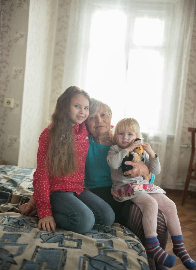 Glückliche Familie, die auf dem Bett sitzt Zwei Mädchen und Großmutter lizenzfreie stockfotos