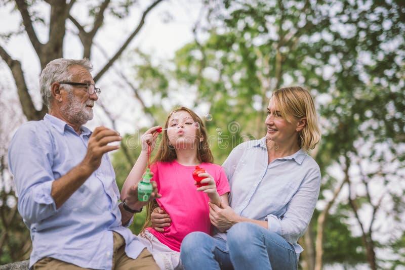 Glückliche Familie im grünen Naturpark auf Sommer lizenzfreies stockfoto
