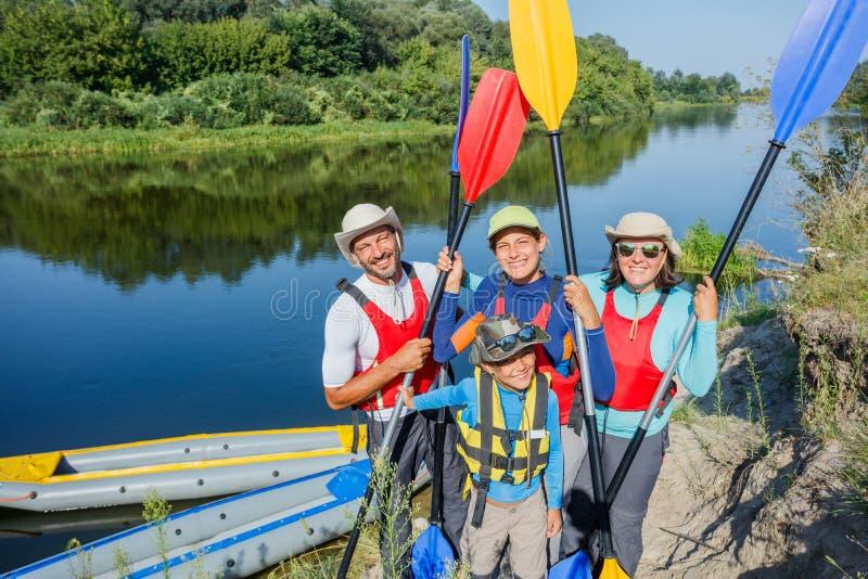 Glückliche Familie mit zwei Kindern, die Kajak genießen, fahren auf schönen Fluss Wenig Jungen- und Jugendlichmädchen, das auf he stockbilder