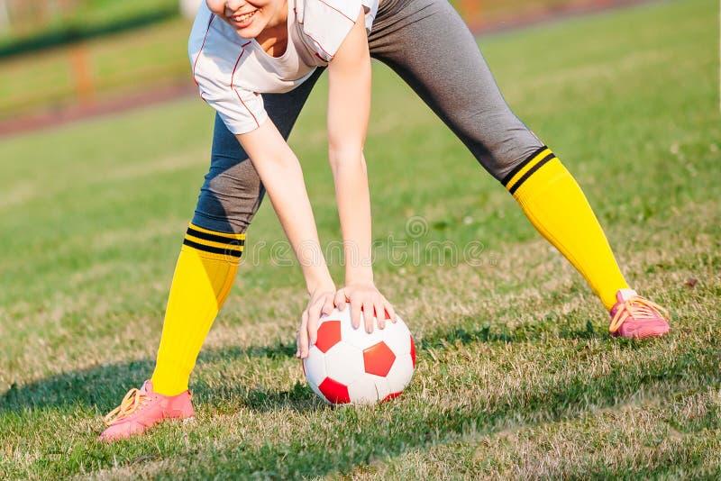 Glückliche junge Frau, die Fußball am Stadion spielt stockfotos