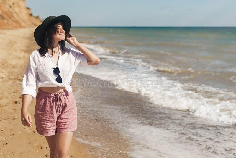 Glückliche junge Frau im weißen Hemd und im Hut gehend auf sonnigen Strand Das dünne Mädchen des Hippies, das nahe Meer mit den W stockfotografie