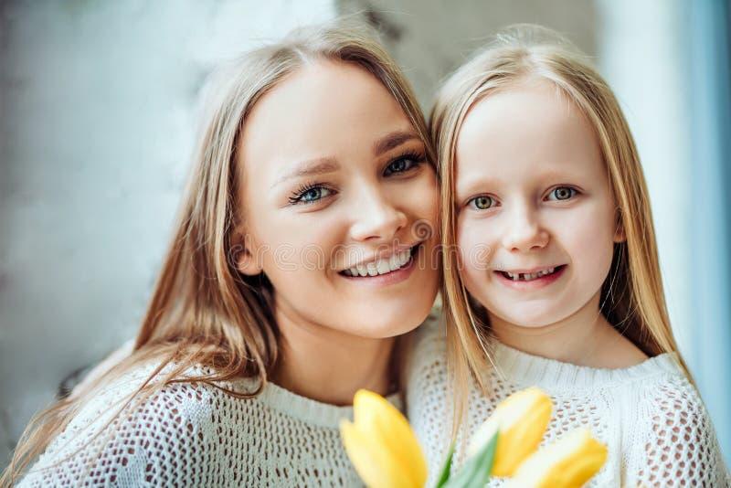 Glückliche liebevolle Familie Mutter und Tochter zusammen mit Blumenstrauß von Tulpen stockbilder