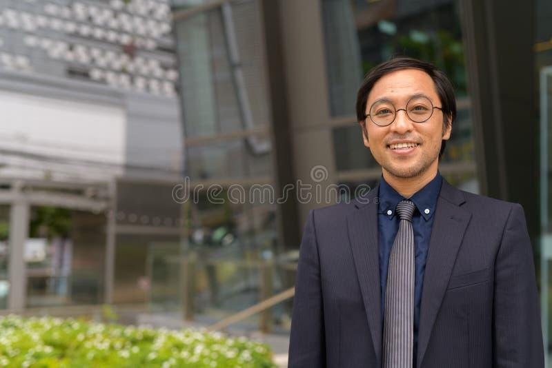 Glücklicher asiatischer Geschäftsmann, der außerhalb des Bürogebäudes lächelt stockbilder