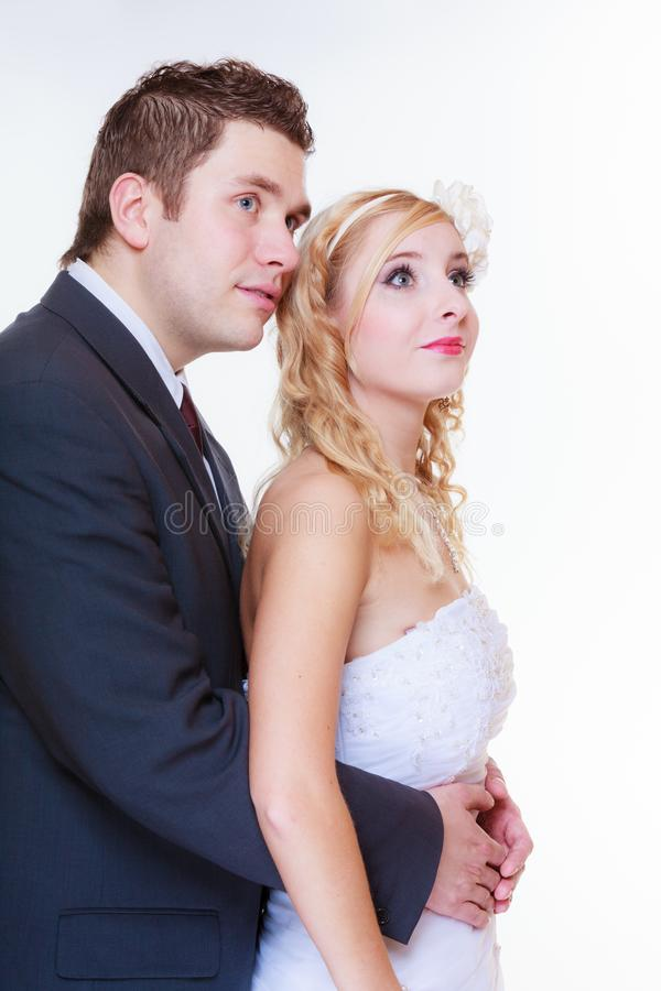 Glücklicher Bräutigam und Braut, die für Heiratfoto aufwirft lizenzfreie stockbilder