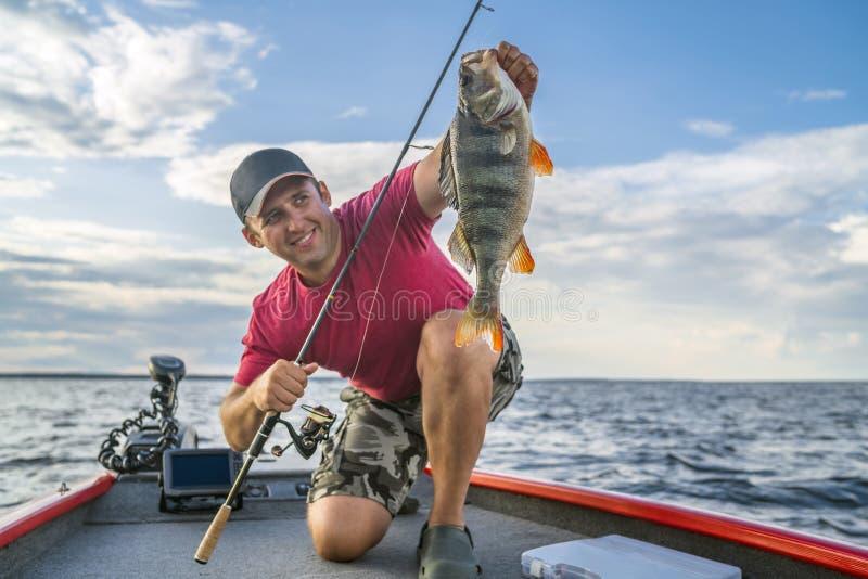 Glücklicher Fischer mit großer Stangenfischtrophäe am Boot lizenzfreie stockfotos