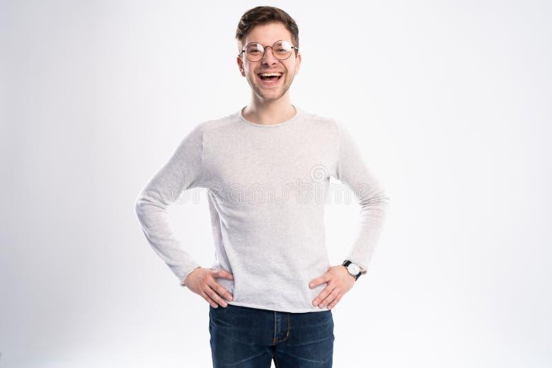 Glücklicher junger Mann Porträt des hübschen jungen Mannes in lächelnder Weilestellung des zufälligen Hemdes gegen weißen Hinterg stockfotografie