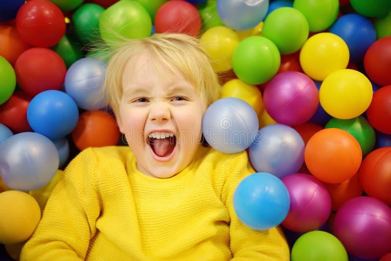 Glücklicher kleiner Junge, der Spaß in der Ballgrube mit bunten Bällen hat Kind, das auf Innenspielplatz spielt lizenzfreies stockfoto