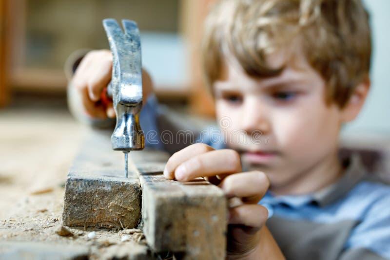 Glücklicher Kleinkindjunge, der bei den Spielzeugwerkzeugen auf Baustelle hilft Lustiges Kind von 7 Jahren Spaß auf dem Errichten stockfoto