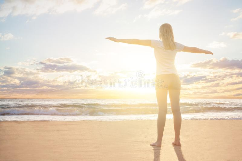 Glücklicher Reisender der jungen Frau genießt ihre Sommerferien in einer Morgensonnendämmerung auf einem tropischen Strand resert lizenzfreies stockfoto