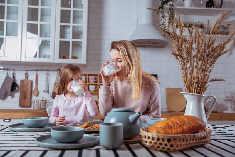 Glückliches kleines Mädchen und ihre schöne junge Mutter frühstücken zusammen in einer weißen Küche Sie trinken Milch und essen P stockfotos