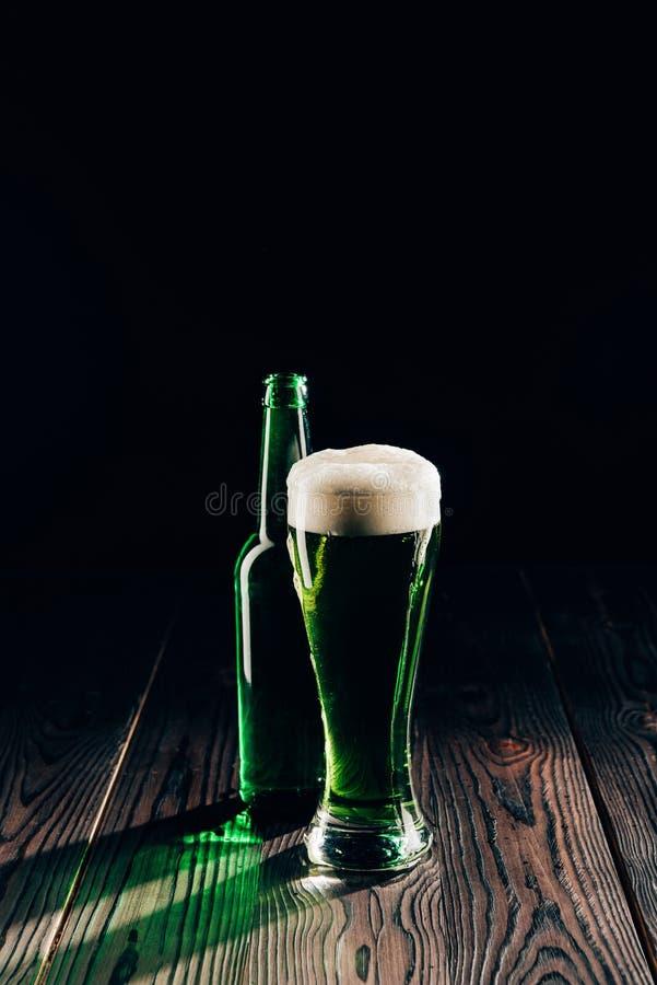 glänsande exponeringsglas och flaska av grönt öl på trätabellen, st-patricks royaltyfria bilder
