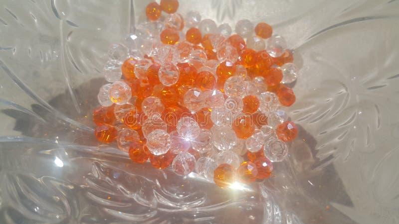 Glänsande, genomskinliga orange färgkristallpärlor eller gemstones i en exponeringsglasbunke royaltyfri fotografi