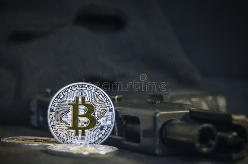 Glänzende Bitcoin-Münze mit Gewehr und schwarzer Maske lizenzfreie stockbilder