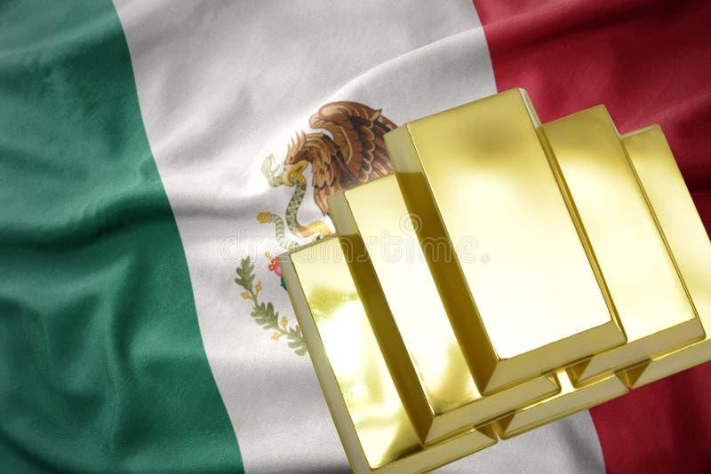 Glänzende goldene Goldbarren auf der Mexiko-Flagge stockfotos