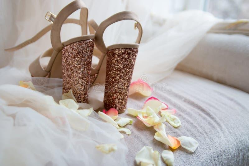 glänzende Goldschuhe auf einem hellen Tulle in den rosafarbenen Blumenblättern lizenzfreie stockfotos