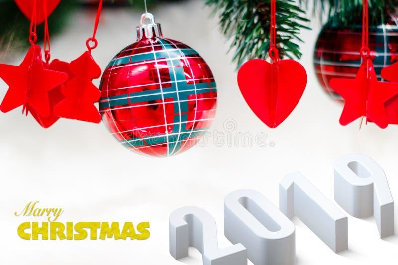 Glänzende rote Weihnachtsbälle, -herz und -sterne auf Weiß mit Kiefer für neues Jahr mit Text 2019 stockfoto
