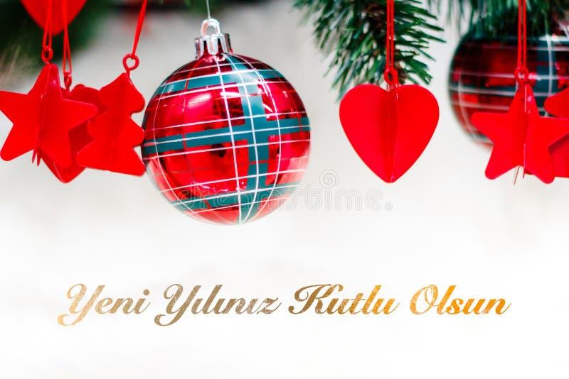 Glänzende rote Weihnachtsbälle, -herz und -sterne auf Weiß mit Kiefer mit Text Yeni-yiliniz kutlu olsun Durchschnittguten rutsch  stockfotografie