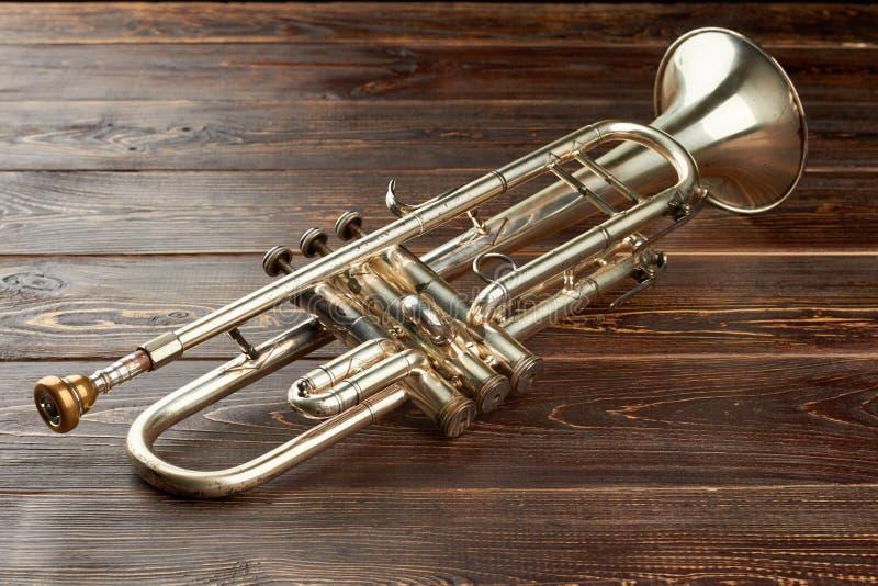 Glänzende Trompete auf braunem hölzernem Hintergrund lizenzfreies stockbild