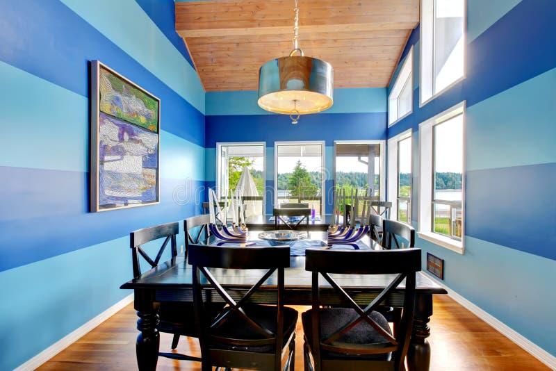 Glänzender dinning Raum mit Blau abgestreiften Wänden lizenzfreie stockfotografie