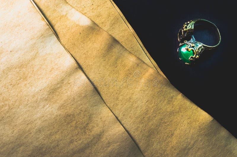 Glänzender grüner Edelstein auf einem Ring und alten leeren Papieren auf schwarzem Hintergrund lizenzfreies stockfoto