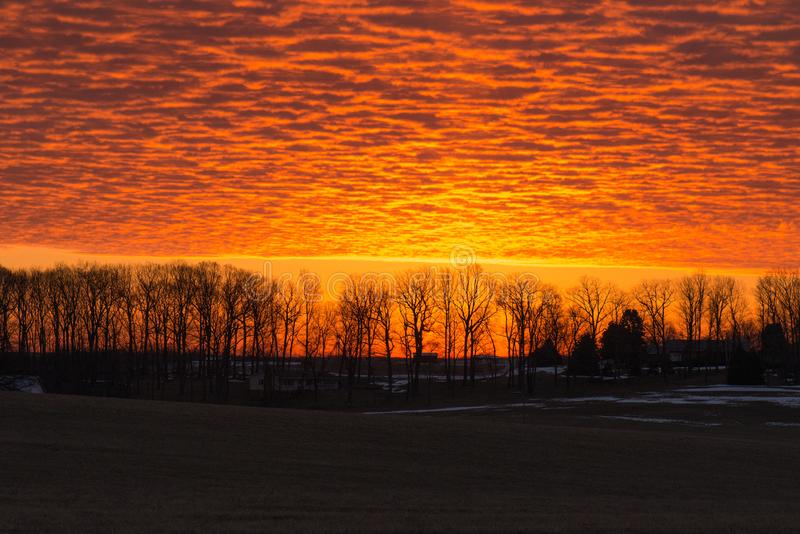 Glänzender orange Sonnenaufgang über senic Landschaft stockfotografie