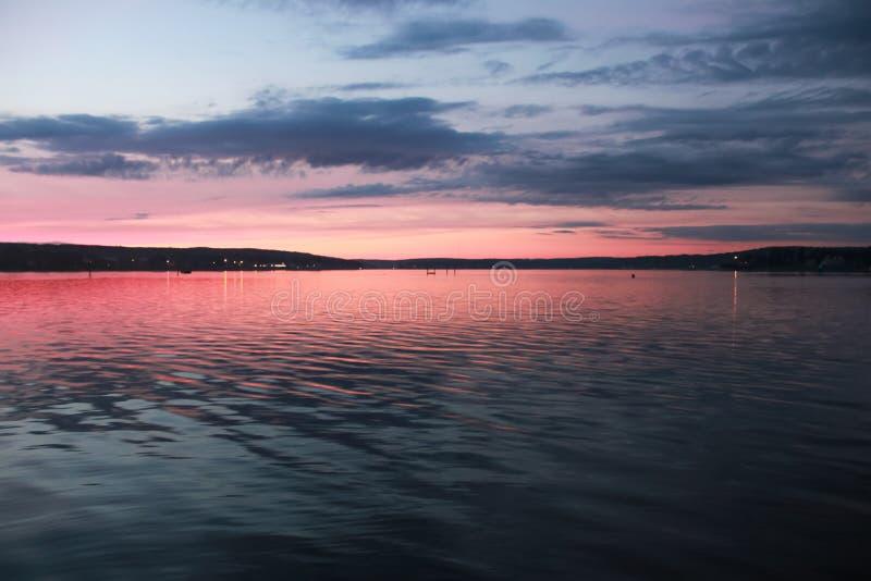 Glänzender rosa Sonnenuntergang auf dem Wasser lizenzfreies stockfoto