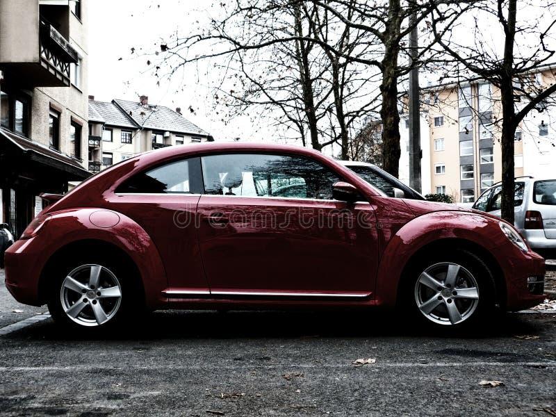 Glänzender Rot VW-Käfer im Parkplatz stockfotografie